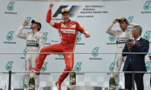 Vettel celebrating first Ferrari win at 2015 Malaysia GP, on podium with Hamilton and Rosberg