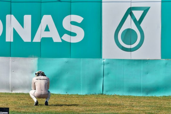 hamilton-squats-aside-the-track-c-mercedes